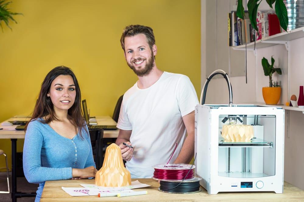 Diseñadores de pie detrás de la máquina de impresión 3D