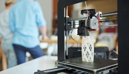 Impresora 3D moderna con modelo arquitectónico