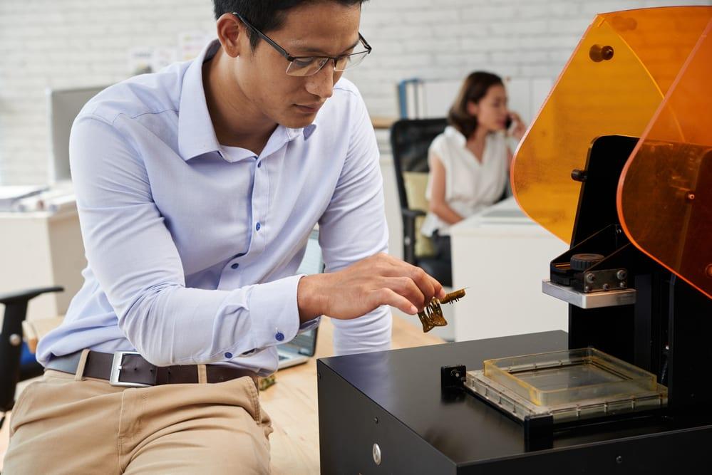 Asiático joven tomando forma de plástico de la impresora 3D - impresoras 3d profesionales